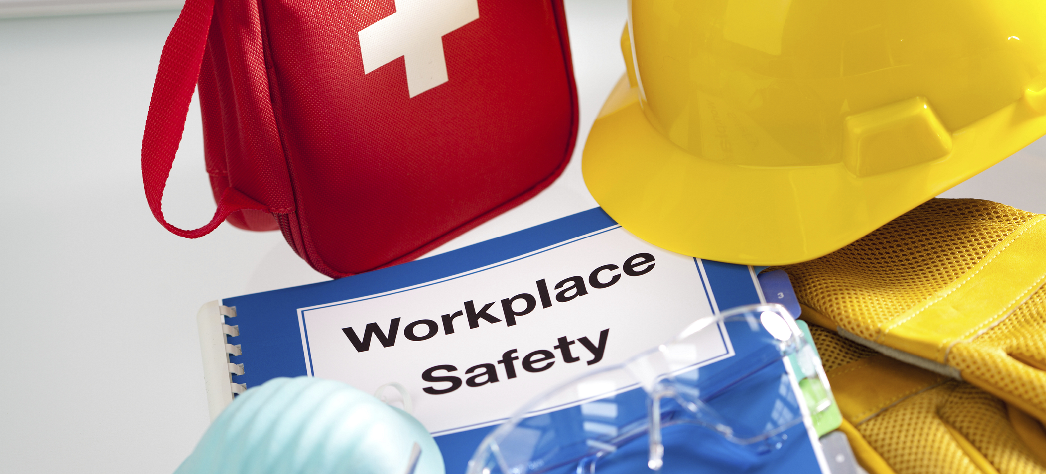 Workplace safety booklet, first aid kit, hard hat, gloves and mask - safety solutions